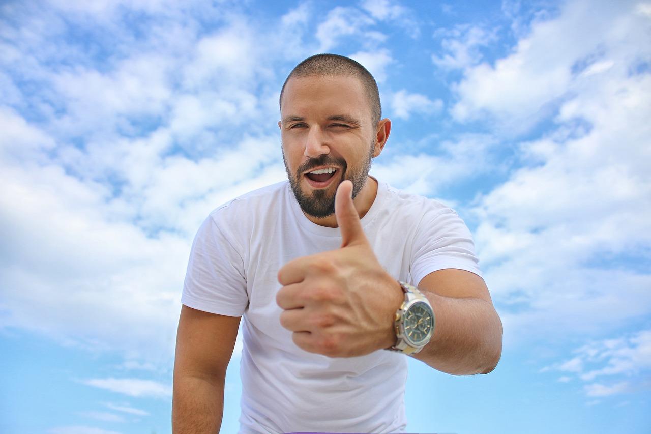 Gutaussehender junger Mann mit teurer Uhr im weißen T-Shirt vor blauem Himmel hät den Daumen hoch.